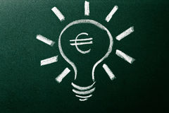 Light bulb as concept of solution for money crisis Royalty Free Stock Image