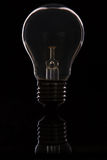 Light bulb back lit macro standing on shiny black surface reflec Royalty Free Stock Photo