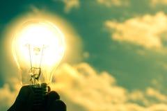 Light bulb on the background of sky. Man on hands holding light bulb on the sky background stock illustration
