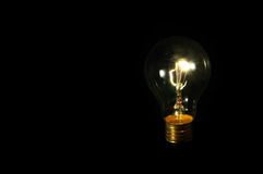 Light bulb on black Stock Images