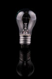 Light bulb on black background, reflection Royalty Free Stock Images
