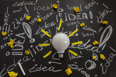 Light bulb on the black chalkboard with titles idea. Light bulb with rays made from yellow stickers on the black chalkboard with titles idea! written by white Stock Images