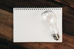 Light bulb on a blank book on a wooden table. Idea and energy saving concept Royalty Free Stock Photos