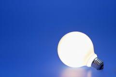 Light bulb on a blue. A lit up light bulb on a blue background Stock Photo