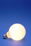 Light bulb on a blue. A lit up light bulb on a blue background Royalty Free Stock Image