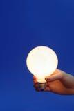 Light bulb on a blue. Female hand holding glowing light bulb on a blue background Stock Image