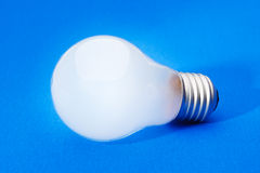 Light bulb on blue Stock Photos