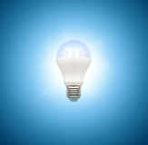 Light bulb on blue background Stock Images