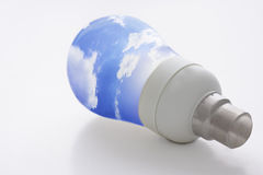 Light bulb and blue sky. Low energy consumption light bulb with blue sky as bulb. Concept for clean, green sustainable energy and energy consumption. Isolated on Royalty Free Stock Photo