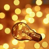 Light Bulb with bokeh. Bulb on gold background with bokeh Royalty Free Stock Photography
