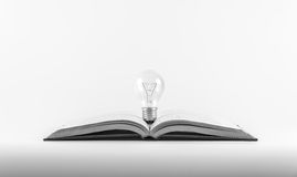 Light bulb on a book. Light bulb on a book, adjust black and white,for a concept of thinking Royalty Free Stock Photo