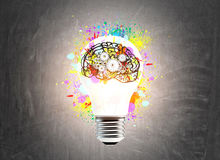 Light bulb and a brain with cogs. Large glowing light bulb sketch is drawn on a chalkboard, There is a small colorful brain icon with cogs on it. Toned image royalty free stock images