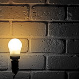 Light bulb and brick wall. Light bulb turn on in room with brick wall Stock Photography