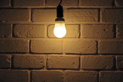 Light bulb and brick wall. Light bulb turn on in room with brick wall Royalty Free Stock Photo