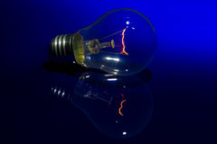 Light bulb with burning filament lay. On blue shiny surface with reflection Stock Photography