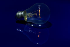 Light bulb with burning filament lay on blue surface with reflec. Light bulb with burning filament lay on blue shiny surface with reflection Royalty Free Stock Photos