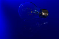 Light bulb with burning filament lay on blue surface with reflec Stock Image