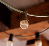 Light bulb on cable against brick wall Stock Photo