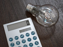 Light bulb and calculator Royalty Free Stock Images