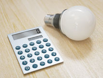 Light bulb and calculator Royalty Free Stock Image