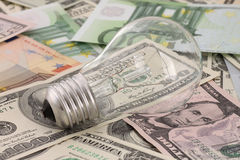 Light bulb on cash Stock Images