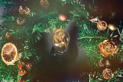 Light bulb in the center of a Christmas wreath. Of fir tree branches and cones with oranges Royalty Free Stock Photo