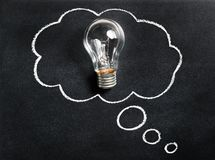 Light bulb on chalkboard. Thinking of new great idea. Brainstorming and creating. Creativity, innovation, inspiration. stock photo
