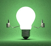 Light bulb character giving thumbs up on green Stock Photography