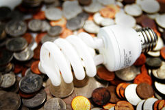 Light bulb and coins Royalty Free Stock Photography