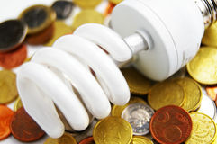 Light bulb and coins Stock Photo