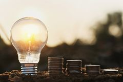 Light bulb with coins stack on soil. saving money accounting. po Stock Photos