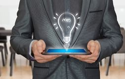Light bulb coming out of a tablet of a businessman Royalty Free Stock Photography