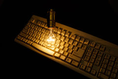 Light bulb and computer keyboard Royalty Free Stock Image
