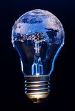 Light bulb covered with ice. Depicting environmental impact concept of electricity efficiently Royalty Free Stock Image