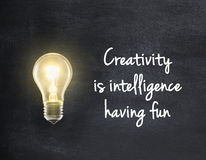 Light bulb with creativity quote. Light bulb lamp on blackboard background with creativity quote Stock Photography