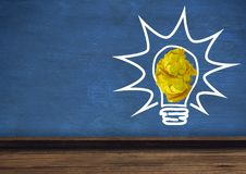 Light bulb with crumpled paper ball in front of blackboard. Digital composite of light bulb with crumpled paper ball in front of blackboard Stock Image