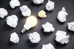 Light bulb and crumpled papers in the black background. Idea stock images