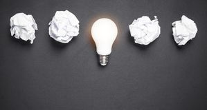 Light bulb and crumpled papers in the black background. Idea. Light bulb and crumpled papers in the black background royalty free stock photo