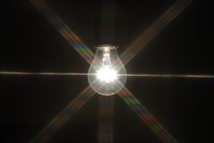 Light bulb in the dark. Rainbow light rays coming from light bulb royalty free stock images