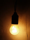 Light bulb on a dark wall Royalty Free Stock Images