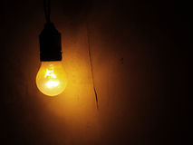 Light bulb on a dark wall Royalty Free Stock Photography