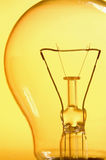 Light Bulb,detail of the filament of a light bulb on yellow background Royalty Free Stock Images