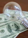 Light bulb on dollar bill heap Royalty Free Stock Photo