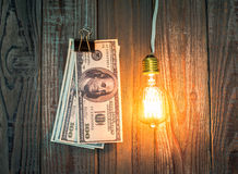 Light bulb and dollar hang Stock Images