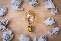 Light bulb and  drawing graph inside with Crumpled paper on wood Stock Photos