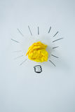 Light bulb drawn around crumbled yellow paper Stock Images