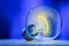A light bulb that is emitting a flash of yellow light inside it, isolated on blue shade. Bulb on a wooden table with blue nuances royalty free stock photography