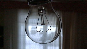 Light bulb with filament close-up in a dark room. Light bulb with a filament close-up in a dark room stock footage