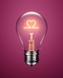 Light Bulb with Filament Forming a Heart Icon. On purple background Royalty Free Stock Photography