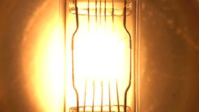 Light bulb filament glow slow flashing tungsten lightbulb. Floodlight flashes slow motion.  stock video